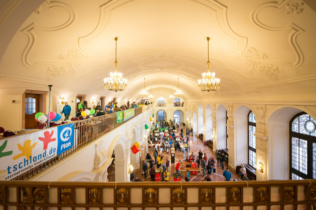 Von der Empore blickt man auf die Oberen Wandelhalle und sieht Tische mit Spielenden. In der linken Bildseite sieht man auf der Empore Kinder in kreative Arbeit vertieft. Luftballons schmücken die Szene.