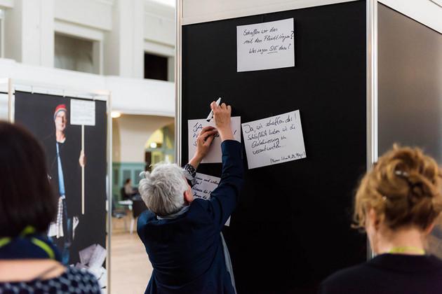 Eine Frau mit grauen Haaren pinnt einen weißen Zettel an eine schwarze Pinnwand