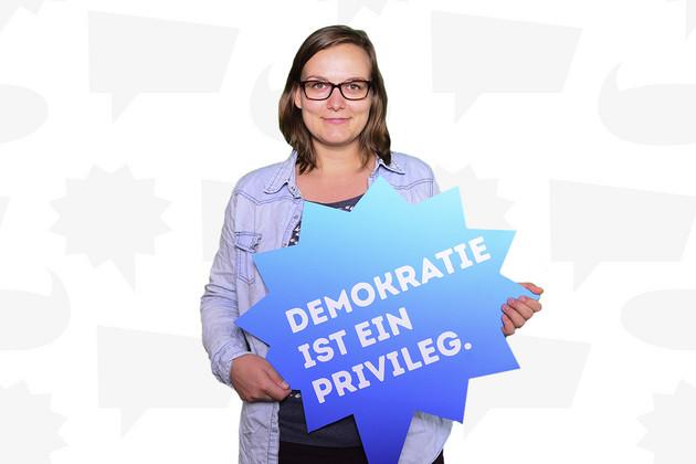 """Eine Frau hält eine Schild mit dem Statement """"Demokratie ist ein Privileg.""""."""