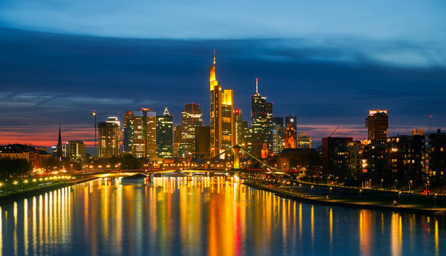 In später Abendstimmung sieht man die hell beleuchteten Hochhäuser Frankfurts im Main sich spiegeln