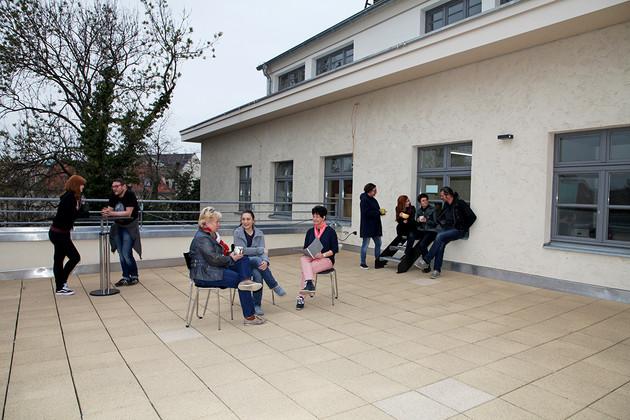 Sanierte Terrasse der Bibliothek mit Sitzgelegenheiten und Menschen, die sich unterhalten.