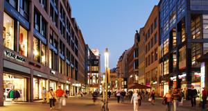 Einkaufsstraße Petersstraße mit beleuchteten Geschäften und Einkaufenden zum Abend