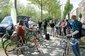 Bild wird vergrößert: Viele Leute mit Fahrrädern stehen auf einem Fußweg und unterhalten sich.