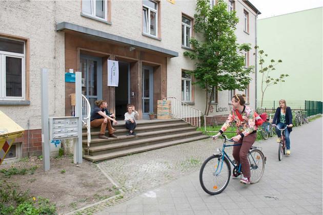 Zwei Fahrradfahrer fahren auf dem Fußweg vor einem Gebäude. Auf der Treppe vor dem Gebäude sitzen drei Menschen. Eine Person grüßt die Fahrradfahrer.