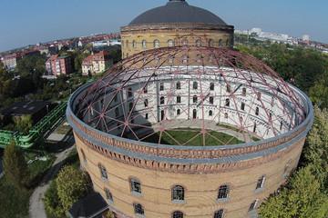 Bild wird vergrößert: Luftbild eines alten riesigen runden Gasometers mit offenen Dach.