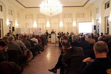 Bild wird vergrößert: Zuhörer in einem Saal hören einem Redner zu, der die Ergebnisse der Jugendwerkstatt zum Leipziger Freiheits- und Einheitsdenkmal vorstellt.