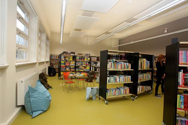 Blick in die neue Kinderbibliothek der Bibliothek Plagwitz, großer Raum mit grünem Fußboden, vielen Regalen, kleinen Tischen, bunten Stühlen und Sitzsäcken.