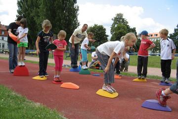 Bild wird vergrößert: Kinder beim Geschicklichkeitsspiel auf dem Sportplatz