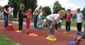 Kinder beim Geschicklichkeitsspiel auf dem Sportplatz