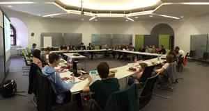 Das Leipziger Jugendparlament bei einer Sitzung. Die Mitglieder sitzen sich gegenüber an Tischen, die zu einem großen Viereck aufgestellt sind.