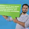 """Ein junger Mann hat sich mit dem Statement """"Demokratie ist halt nicht einfach. Demokratie ist manchmal mühsam. Das macht sie umso kostbarer."""", welches auf einer grünen Sprechblase steht, fotografieren lassen."""