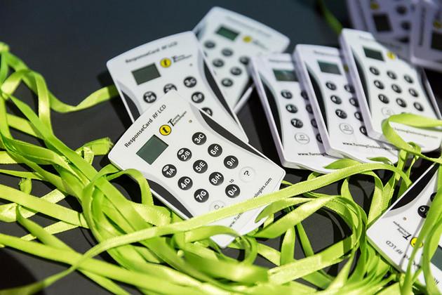 Nahaufnahme von kleinen weißen elektronischen Abstimmungsgeräten, an denen jeweils ein grünes Band befestigt ist.