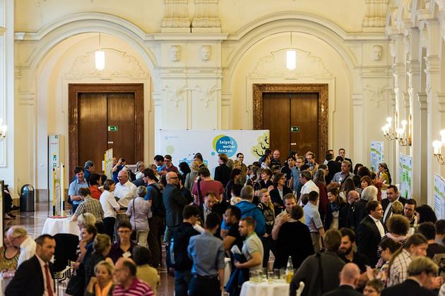 Blick von oben auf ca. 250 Menschen, die vor Ausstellungswänden diskutieren