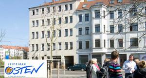 """Gruppe von Menschen steht vor einem Haus und unterhält sich. Auf dem Bild ist das Logo """"Leipziger Osten""""."""