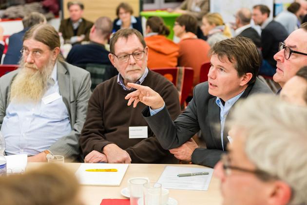 Drei Herren sind an einem Tisch, einer gestikuliert. Dahinter sind weitere Tische mit darum sitzenden Menschen.