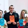 Zwei Männer und eine Frau lassen sich mit Karten fotografieren, auf denen Smileys abgebildet sind. Der Mann links und die Frau rechts halten eine blaue Karte mit lachendem Smiley hoch, der Mann in der Mitte eine orange Karte mit traurigem Smiley.