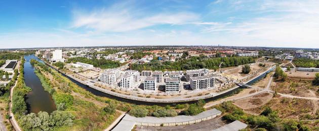 Blick über das gesamte neue Baugebiet am Lindenauer Hafen im Weitwinkel, links im Bild die Wasserfläche