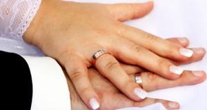 Hände von Braut und Bräutigam mit Eheringen