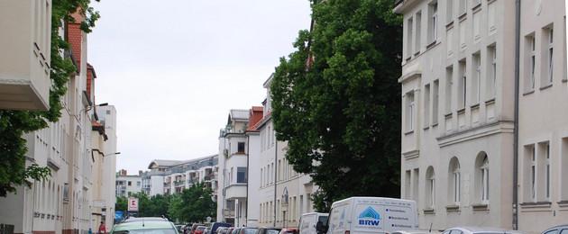 Eine typische Straße in Großzschocher. Links und rechts sind Autos geparkt.