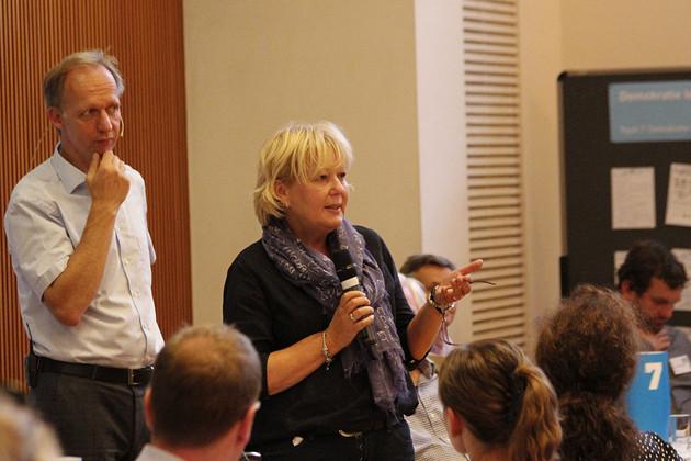 Patra Hochtritt steht mit einem Mikrofon in der Hand und redet zu den Zuhöreren
