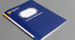 Die Angebote des Schulmuseums, zusammengefasst in einer Broschüre. Blaue Broschüre in Anmutung eines Schulheftes mit Beschriftungsetikett.