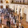 Blick in die obere Wandelhalle im Rathaus, in der viele Menschen an Ausstellungstafeln stehen