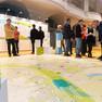 Blick von unten auf eine große Stadtkarte am Boden, daneben stehen einige Menschen