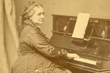 Bild wird vergrößert: alte vergilbte Fotografie von der älteren Clara Schumann am Klavier sitzend und dem Betrachter zugewandt
