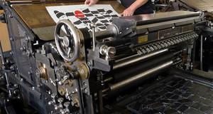 Jemand demonstriert die Schnellpresse im Museum für Druckkunst.