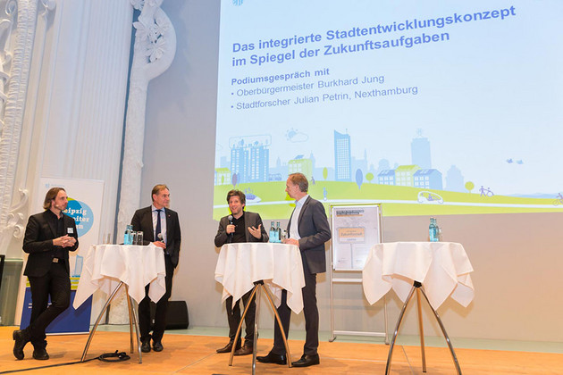 Oberbürgermeister Burkhard Jung und Urbanist Julian Petrin diskutieren auf dem Podium über die Zukunft der Städte.