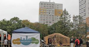 """Blick auf das Gelände des Bunten Mockauer Sommers mit Pavillons und einer großen Plane mit dem Schriftzug """"Bunter Mockauer Sommer"""". Im Hintergrund Hochhäuser"""