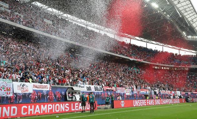 Zu sehen ist der Fanblock von RB Leipzig in der Red Bull Arena Leipzig. Es regnet rotes und weißes Konfetti.