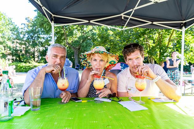 Zwei Männer und eine Frau mit Hut in der Mitte sitzen an einem Tisch, vor sich einen gelb-roten Cocktail, aus dem sie mit einem Strohhalm trinken.