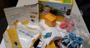 Ausgepackte Babybox mit Geschenke für Neugeborene in Leipzig. Z. B. ein Lätzchen, Schühchen, Infomaterial und ein Babykalender