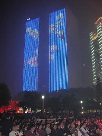 zwei Hochhäuser die nachts blau mit weißen Blumen illuminiert sind
