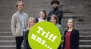 """Sechs junge Menschen stehen auf einer Treppen und schauen freundlich in die Kamera. In einem grünen Kreis über dem Bild steht """"Triff uns""""."""