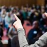Im Vordergrund sind die Schulter und Hände einer Gebärdensprachdolmetscherin zu sehen. Im Hintergrund sitzen die Teilnehmerinnen und Teilnehmer im Plenum.