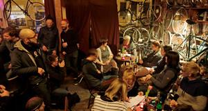 Eine kultige Bar mit vielen Fahrrädern an den Wänden. Wolf Schmid liest im Kreis von Zuhörern aus seinem Buch vor.