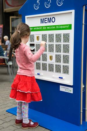 Ein Kind spielt an einem Memory auf dem Markt Leipzig