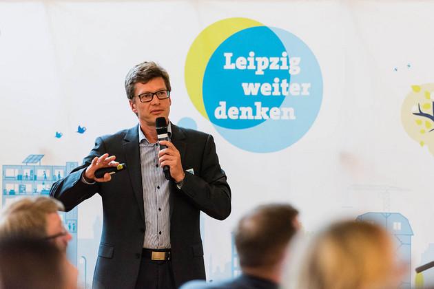 """Ein Herr im Jackett hält vor einem """"Leipzig weiter denken""""-Plakat einen Vortrag"""