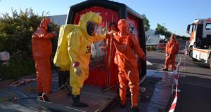 Kameraden der Freiwilligen Feuerwehr bereiten nach einem Gefahrguteinsatz einen Feuerwehrmann unter Chemikalienschutzanzug für die Dekontamination in einem speziellen Zelt vor.
