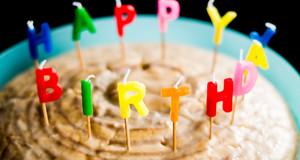 Geburtstagskuchen mit bunten Happy-Birthday-Kerzen