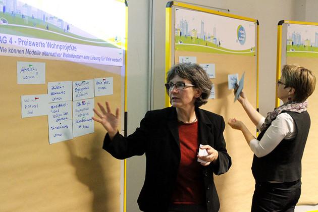 Eine Moderatorin pinnt blaue Karten an eine Wand
