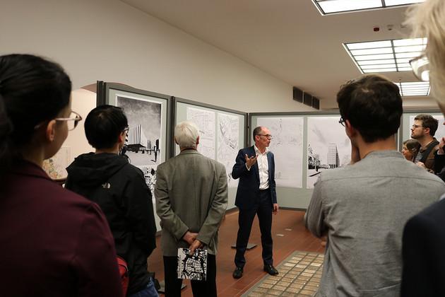 Ein Mann spricht zu Publikum. Er steht vor Ausstellungstafeln.