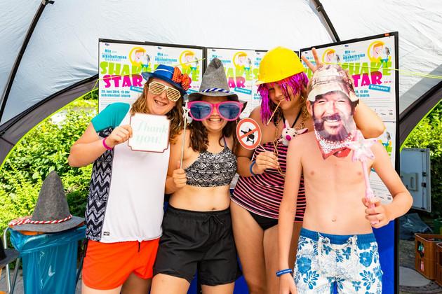 vier Jugendliche, mit Perücken, Masken und Hüten vor einer Wand mit Plakaten vom Wettbewerb
