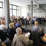 Rund 80 Menschen sitzen im Publikum in einem hellen Raum und hören einem Redner zu