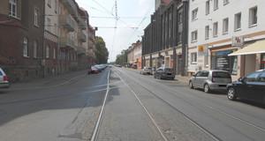 Das Foto zeigt den Straßenquerschnitt der Ratzelstraße in Höhe der Einmündung Hermann-Meyer-Straße: Gleisanlagen, Fahrbahn, Parkstellflächen und Gehwege. Die Fahrbahn weist großflächige Rissbildungen sowie Schlaglöcher auf.