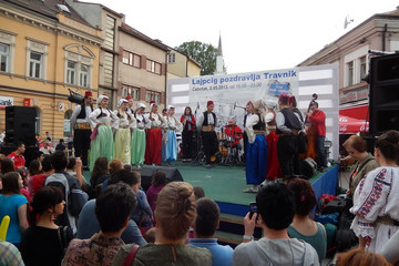 Bild wird vergrößert: Festbühne mit Band und traditionell gekleideten Tänzern, im Vordergrund Zuschauer