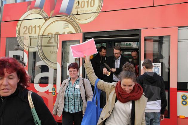 Eine Gruppe von Menschen ströhmt aus einer Straßenbahn. Unter ihnen eine junge Frau mit gesenktem Blick und erhobenem roten Blatt. Sie führt die Gruppe an.