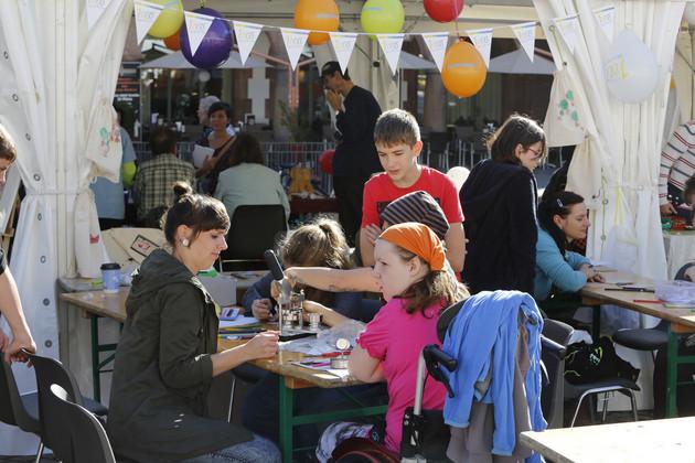 An einem Stand basteln Kinder an zwei Tischen. Zwei Kinder schauen zu.